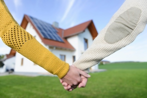Couple holding hands in front of new home, close up