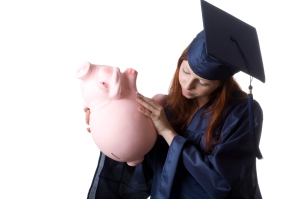 A graduate trying to remove some saved money from her piggy bank. Isolated on white.